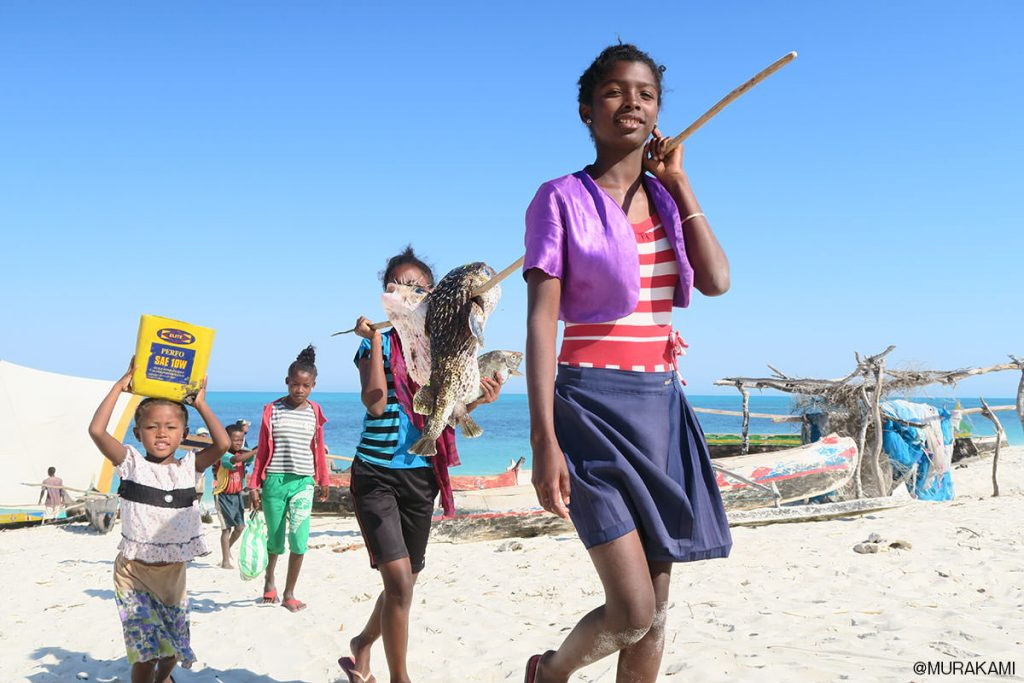 獲ってきた魚を運ぶ女の子達。
