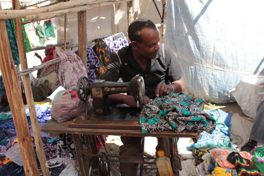年代物のミシンで服を仕立てたり補修するテイラーのおじさん