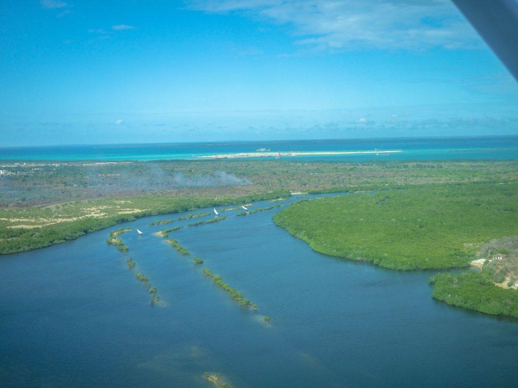 空からの景色。マングローブに覆われたラム島が見えてきました。三角帆のダウ船の姿が見えます。